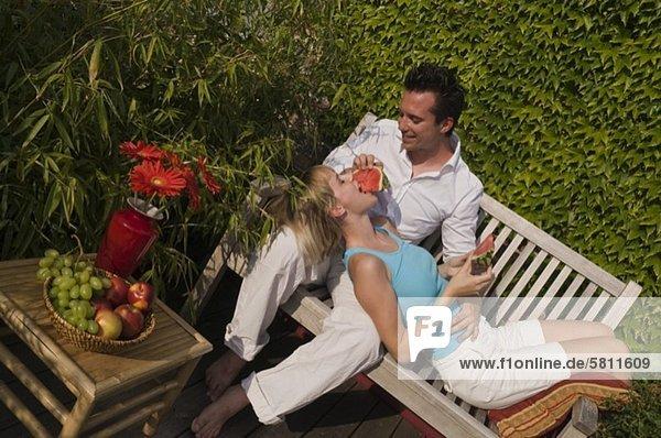 Junger Mann füttert seine Freundin mit einer Wassermelone