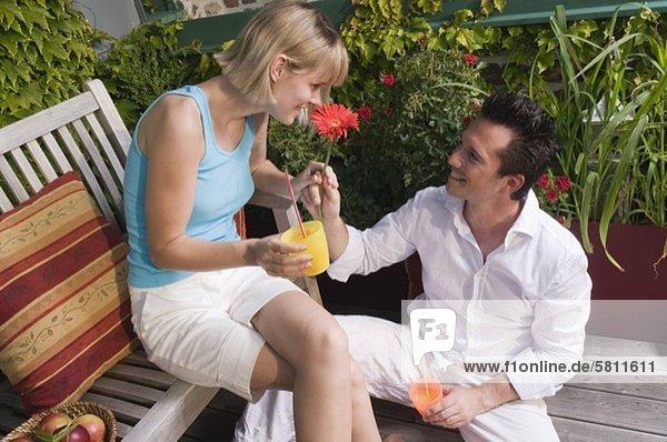 Junger Mann schenkt seiner Freundin eine Blume