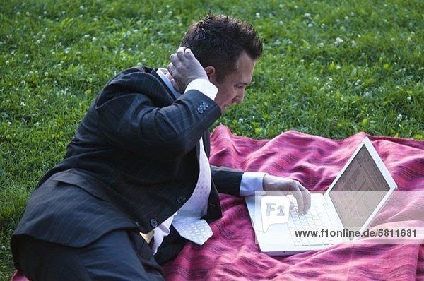 Geschäftsmann benutzt Laptop auf einer Decke