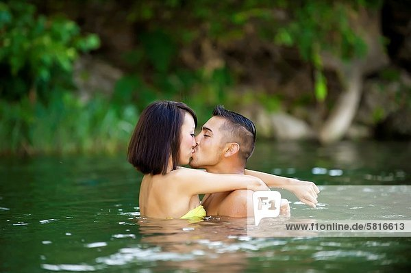 Young couple in love - Asian woman  20 years old  Korean Ethnicity  hispanic man  22 years old  location Frio River near Leakey  Texas  USA