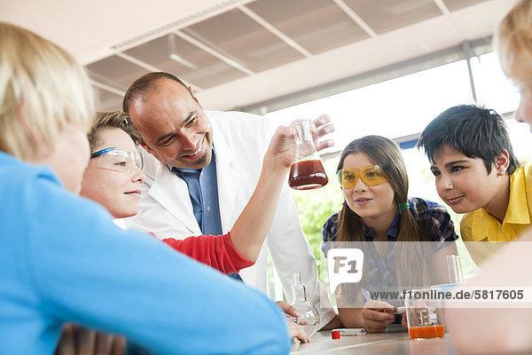 Lehrer und Schüler experimentieren im Chemieunterricht