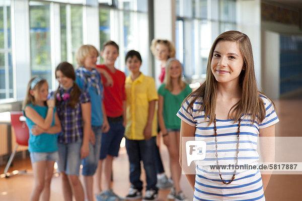Lächelnde Teenagerin vor einer Gruppe von Schulkindern