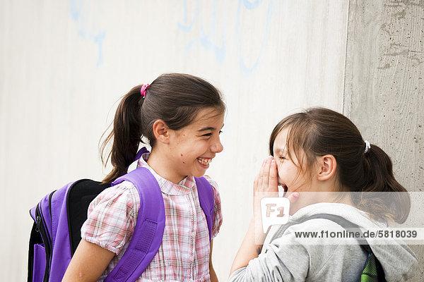 Zwei lachende Mädchen schauen sich an