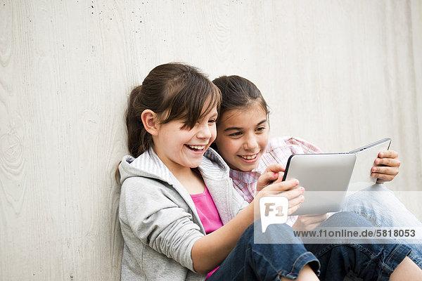 Zwei fröhliche Mädchen mit einem Tablet PC