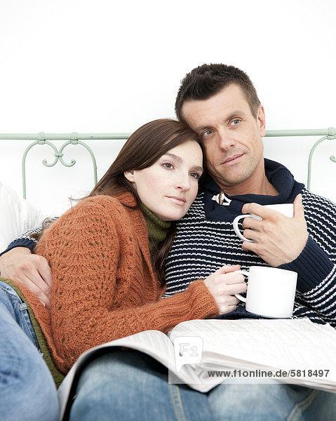 Porträt des jungen Paares liegen im Bett zusammen halten Tassen
