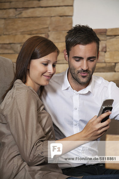 young couple sharing message on mobile phone at restaurant