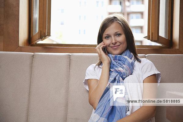 Porträt der jungen Frau sitzen am Fenster im Gespräch auf Handy