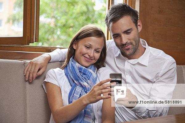 junges paar Blick auf Display des Mobiltelefons