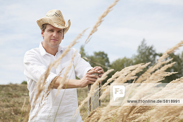 portrait of young man with straw hat in field