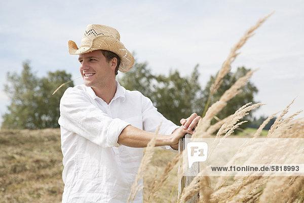 Porträt des jungen Mann mit Strohhut im Feld