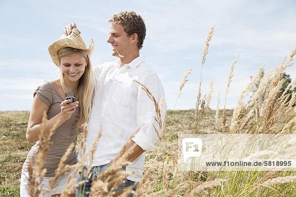 Porträt des jungen Paares im Feld Frau Lloking im Display des Mobiltelefons