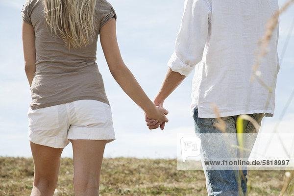 junges Paar halten Hände in Feld