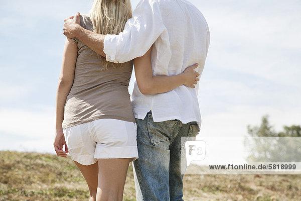 Rückansicht des jungen Paares stehen im Feld