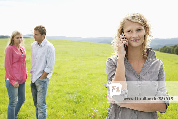 young woman talking on mobile phone on meadow
