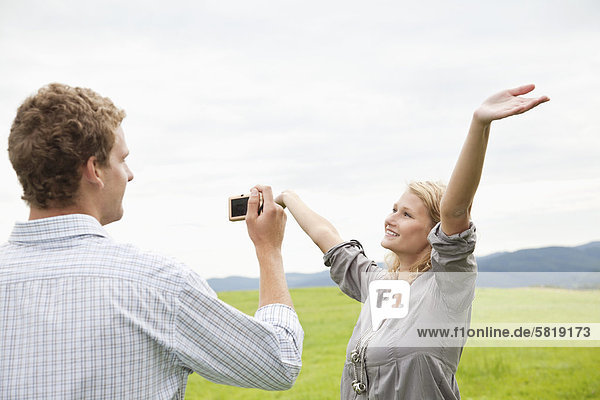 young man taking picture of young woman with digital camera