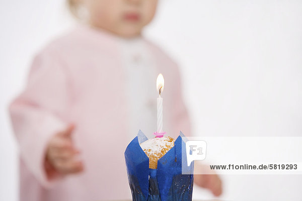 candle burning on muffin to celebrate baby´s first anniversary