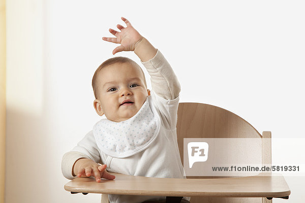 portrait of baby sitting in high chair waving