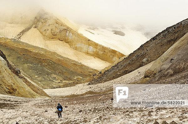 Wanderer zu Fuß durch den Canyon mit Schwefel Sedimente in Mutnowski Vulkan Gebiet auf Kamtschatka