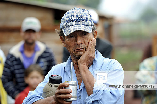 'Farmer with a worried expression is drinking the Paraguayan national drink ''Terere'' made from mate  he was evicted from his land alongside dozens of other smallholders and their families by investors and now lives in a makeshift hut by the roadside  land grabbing  Carlos Antonio Lopez district  Itapua province  Paraguay  South America'
