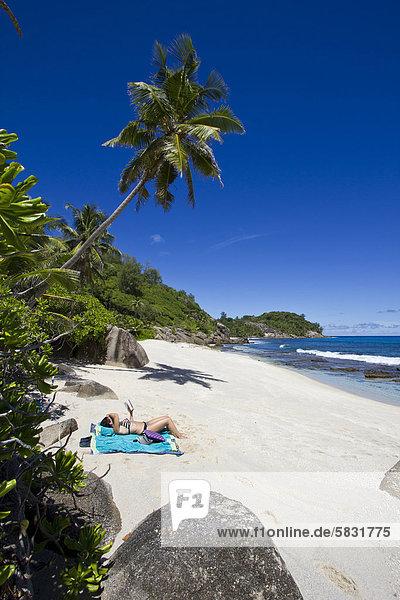 Frau liegt am Strand  Süd-Mahe  Mahe  Seychellen  Afrika  Indischer Ozean