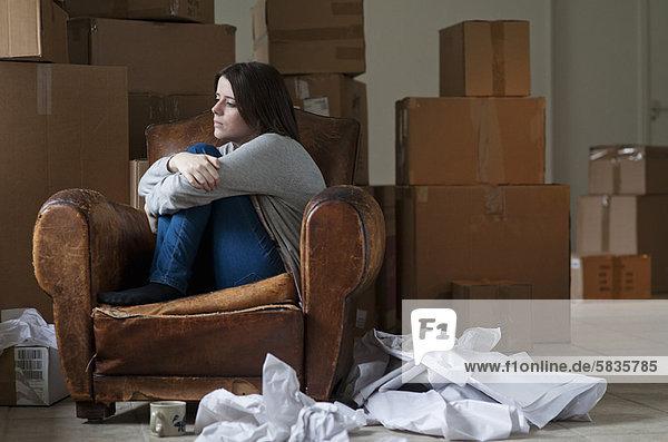 Teenagermädchen im Sessel im neuen Zuhause