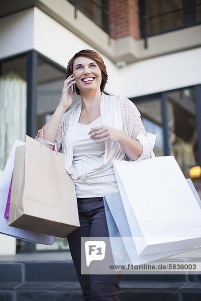 Frau am Handy mit Einkaufstaschen