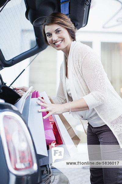 Frau beim Einkaufen im Kofferraum