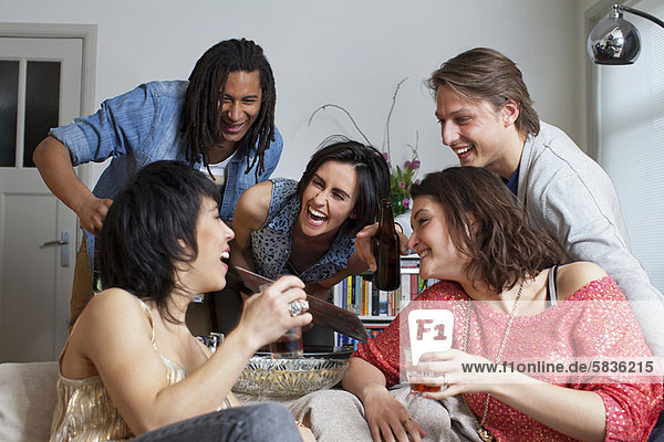 Freunde lachen zusammen im Wohnzimmer