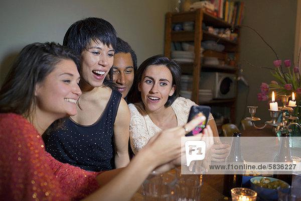 Freunde mit dem Handy am Esstisch