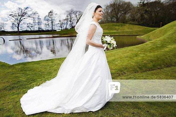 Außenaufnahme  Blumenstrauß  Strauß  tragen  Braut  lächeln  freie Natur