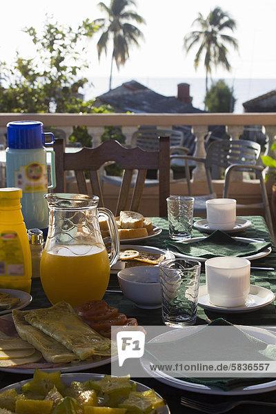Teller und Gläser mit Essen am Tisch