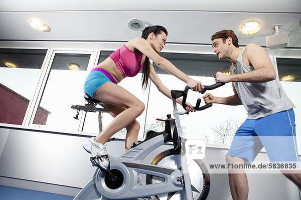 Frau arbeitet mit Trainerin im Fitnessstudio