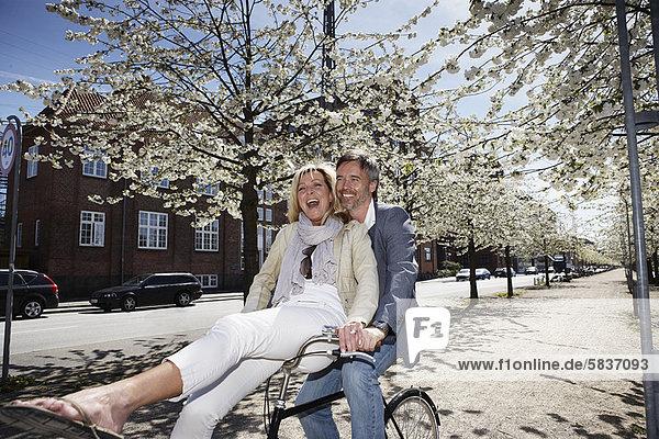 Mann fährt mit Freundin auf dem Fahrrad