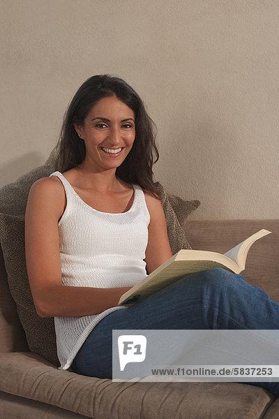 Frau  Couch  Buch  lächeln  Taschenbuch  vorlesen