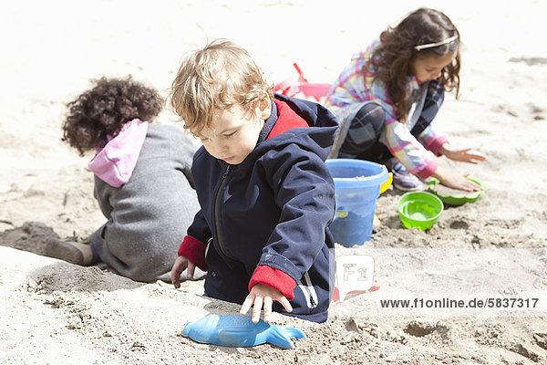 Kinder spielen mit Sand auf dem Spielplatz