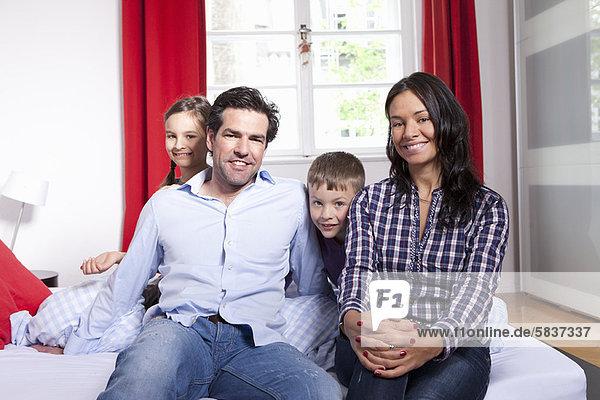 Familie lächelt gemeinsam auf dem Bett