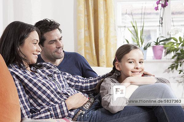 Familie entspannt auf dem Sofa im Wohnzimmer
