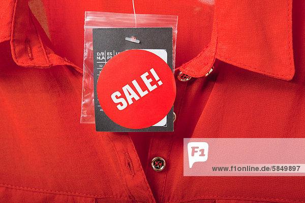 Verkaufsschild auf roter Bluse