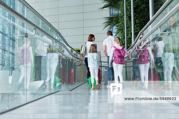 Familie im Flughafen mit Gepäck