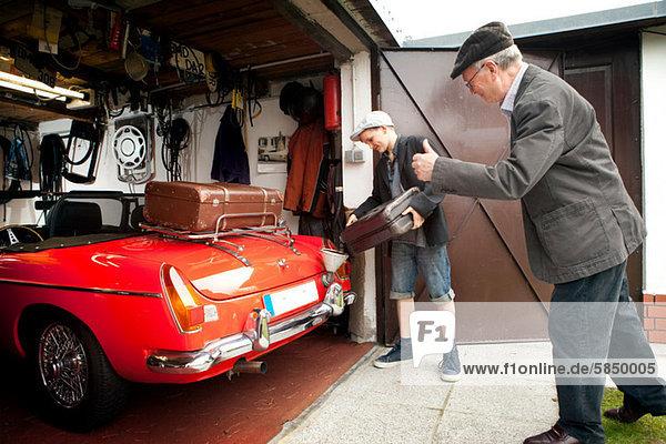 Großvater und Enkel verpacken Oldtimer mit Koffer in Garage
