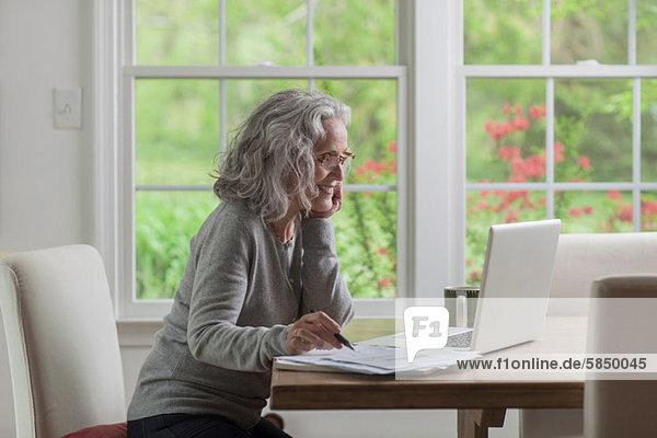 Senior Frau mit Laptop zu Hause