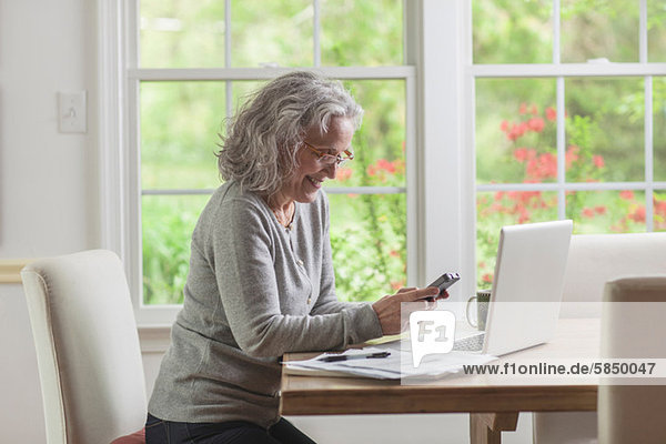 Seniorin mit Smartphone und Laptop zu Hause