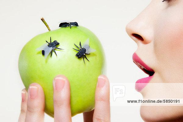 Junge Frau isst Apfel mit Fliegen darauf,  Mund