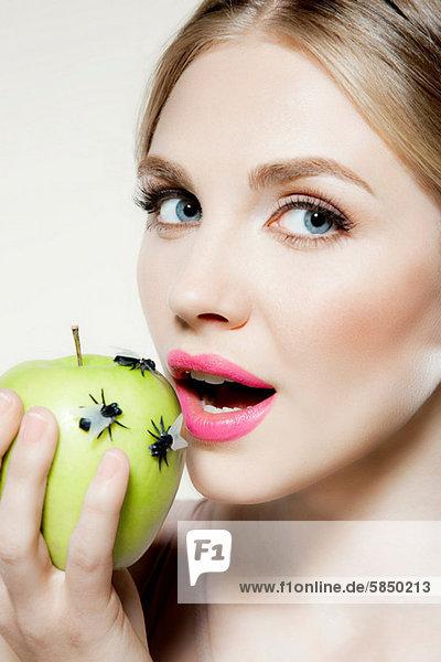 Junge Frau isst Apfel mit Fliegen darauf
