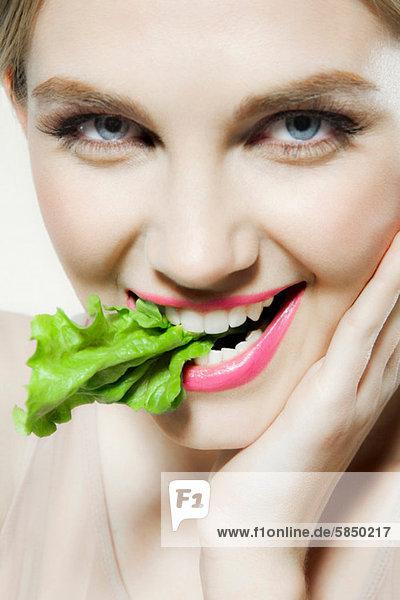 Junge Frau beißt Salat