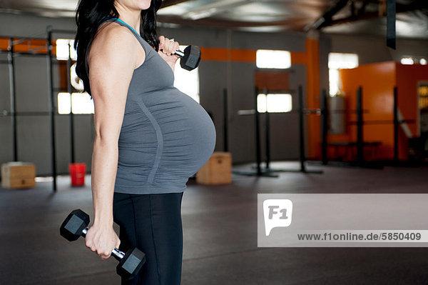 Schwangere junge Frau mit Handgewichten
