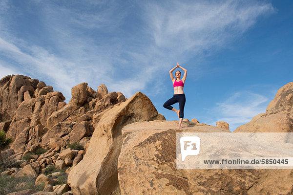 Junge Frau in Baumhaltung auf Wüstenfelsen