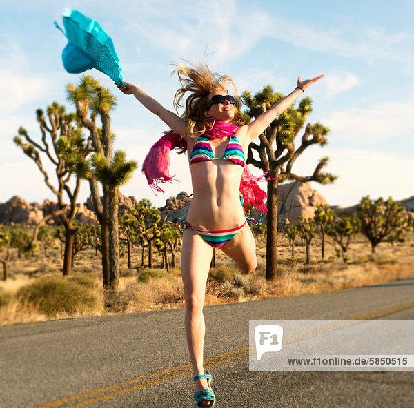 Junge Frau im Bikini mit Armen auf der Wüstenstraße