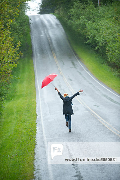 Frau auf leerer Straße mit rotem Regenschirm