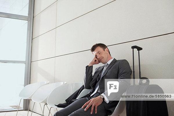 Geschäftsmann mit Gepäck  schlafend